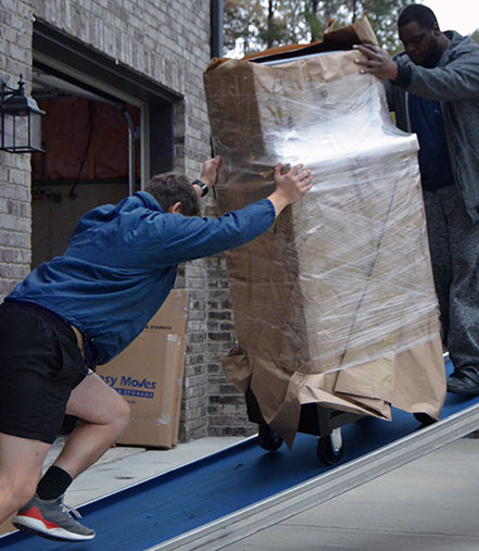 Movers moving tool chest up ramp.